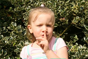 little girl with finger to lips